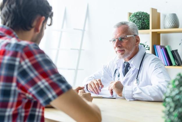 Senior docteur à l'écoute du patient Photo gratuit
