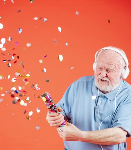 Senior écoute De La Musique Et Des Confettis Photo gratuit