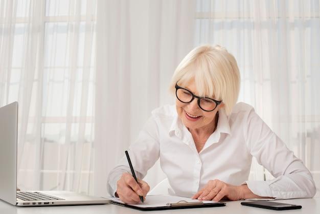 Senior écrit sur un presse-papiers Photo gratuit