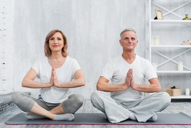 Senior famille couple assis en posture de lotus sur tapis d'yoga gris Photo gratuit