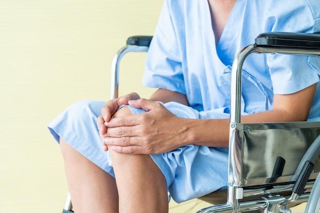 Senior fauteuil roulant asiatique avec douleur au genou Photo Premium