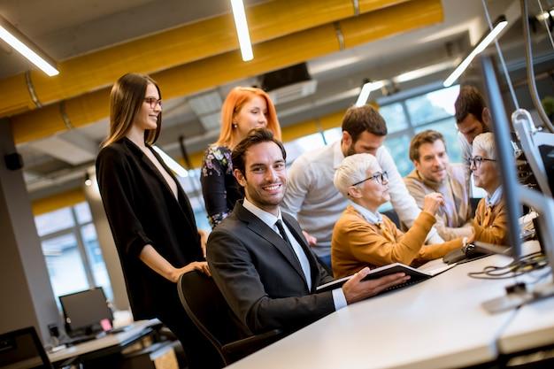 Senior femme d'affaires travaillant avec de jeunes hommes d'affaires au bureau Photo Premium