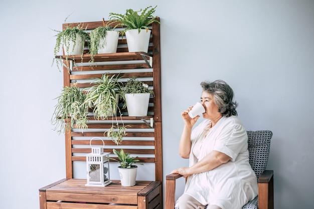 Senior femme assise et buvant du café ou du lait Photo gratuit