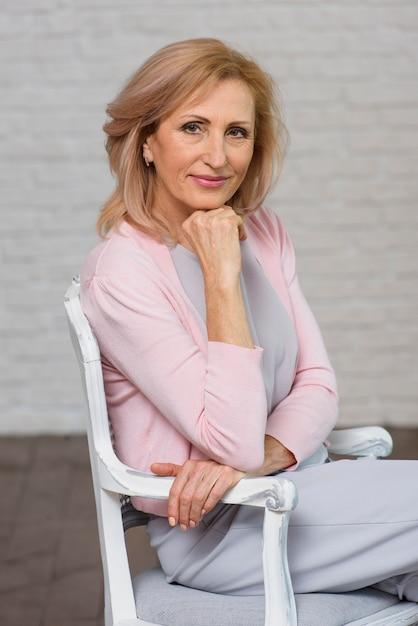 Senior femme assise sur une chaise Photo gratuit