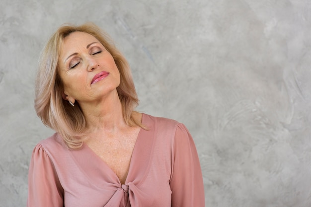 Senior femme aux yeux fermés Photo gratuit
