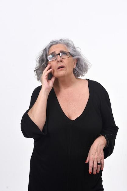 Senior femme ayant un doute ou une question sur fond blanc Photo Premium