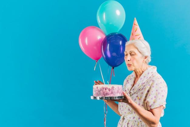 Senior femme avec des ballons et gâteau d'anniversaire soufflant une bougie sur fond bleu Photo gratuit