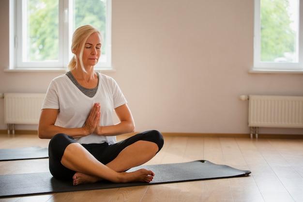 Senior femme blonde pratiquant le yoga Photo gratuit