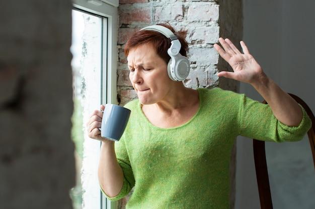 Senior femme chantant à la tasse de café Photo gratuit