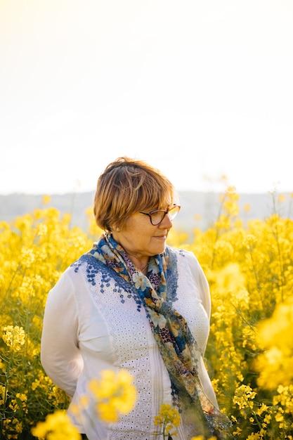 Senior femme dans un champ de fleurs jaunes Photo Premium