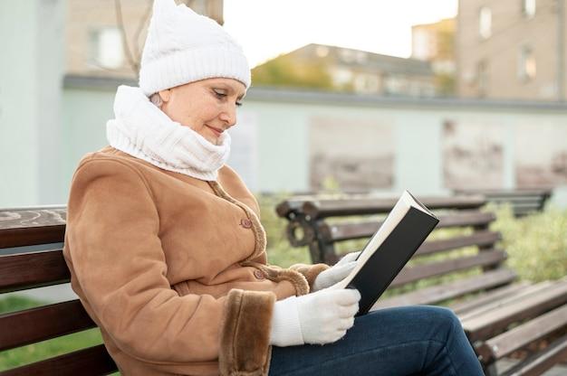 Senior femme dans le temps de lecture du parc Photo gratuit