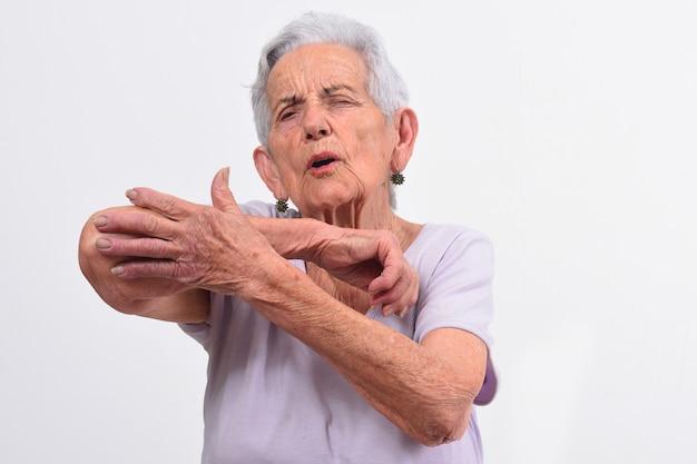 Senior femme avec douleur au coude sur blanc Photo Premium