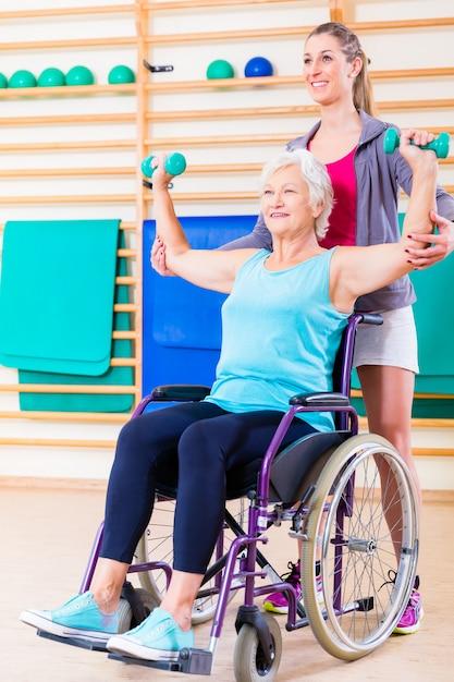 Senior femme en fauteuil roulant faisant de la physiothérapie Photo Premium