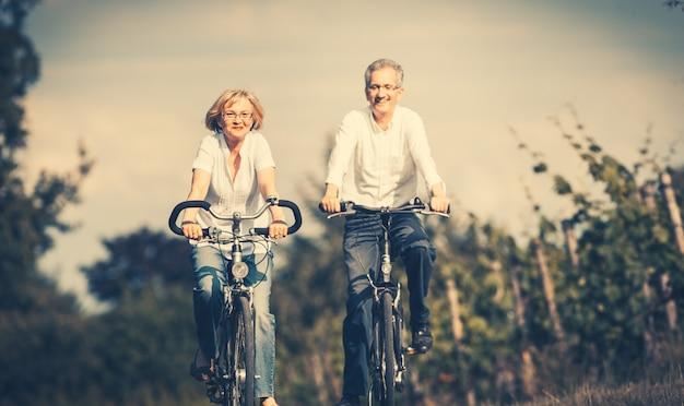 Senior femme et homme à vélo en été Photo Premium