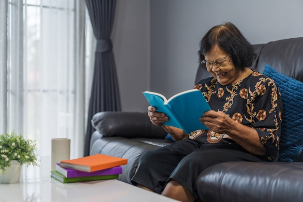 Senior femme lisant un livre et rire dans le salon Photo Premium