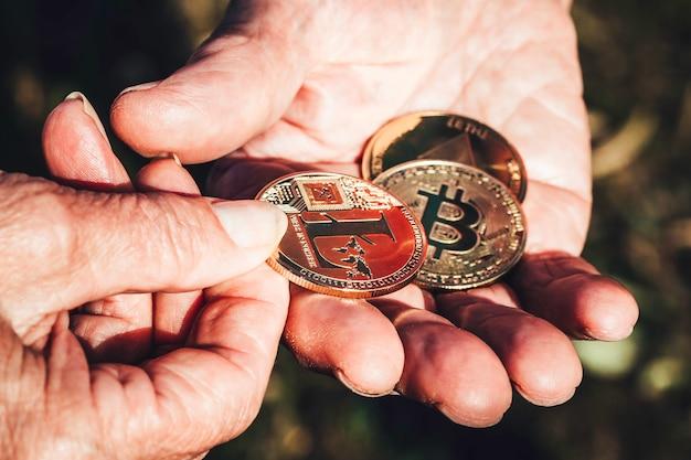 Senior femme main tient pièce de monnaie crypto en bref donnant à main d'homme senior Photo Premium