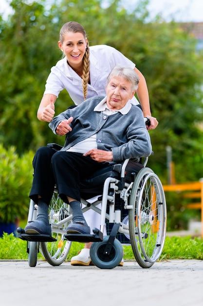 Senior femme en maison de retraite avec infirmière dans le jardin Photo Premium