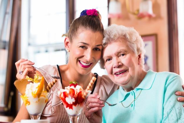 Senior femme et petite-fille s'amusant à manger des sundae de crème glacée au café Photo Premium
