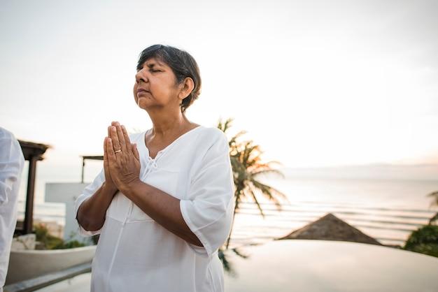 Senior femme pratiquant le yoga le matin Photo Premium