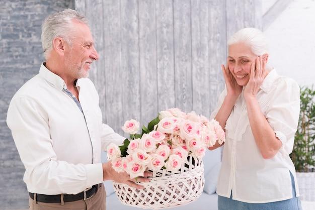 Senior femme surprise en regardant panier de roses tenu par son mari heureux Photo gratuit