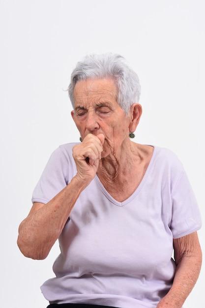 Senior femme avec toux sur fond blanc Photo Premium