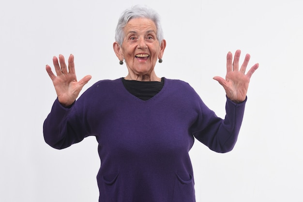 Senior femme avec un visage surpris et mains surélevées sur fond blanc Photo Premium