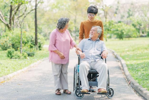 Senior homme asiatique en fauteuil roulant avec sa femme et son fils Photo Premium