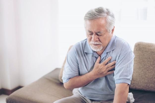 Senior homme asiatique souffrant de douleurs dans la poitrine, crise cardiaque à la maison Photo Premium