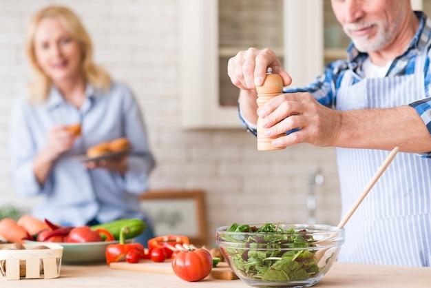 Senior homme assaisonner la salade de légumes verts et sa femme tenant les muffins à la main en toile de fond Photo gratuit