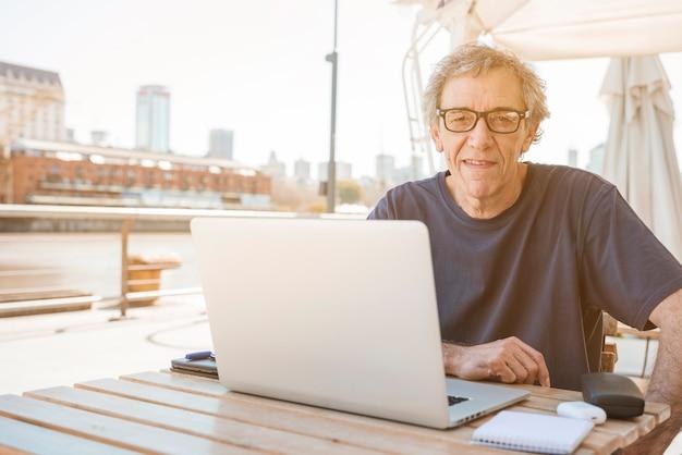 Senior homme assis au restaurant avec ordinateur portable sur la table Photo gratuit