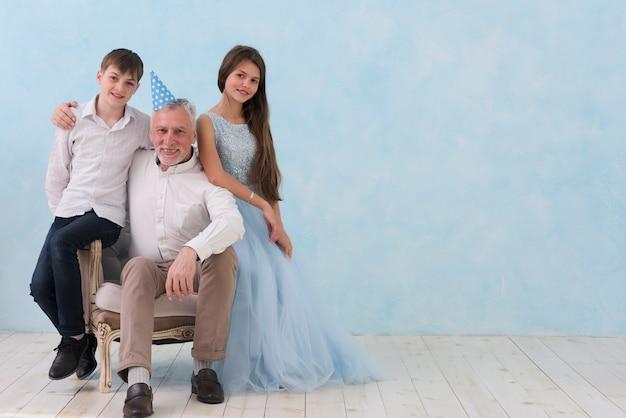 Senior homme assis ses petits-enfants sur un fauteuil en regardant la caméra Photo gratuit