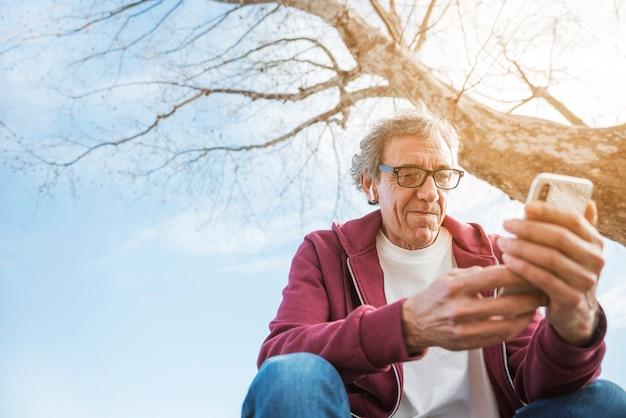 Senior homme assis sous l'arbre à l'aide de téléphone portable avec des écouteurs bluetooth sur ses oreilles Photo gratuit