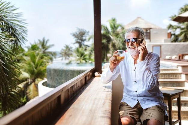 Senior homme au téléphone prendre un verre Photo Premium