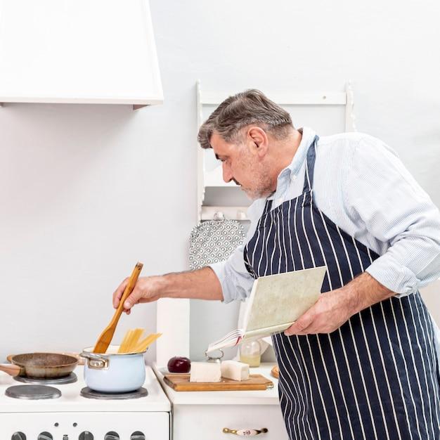 Senior homme cuisine avec une cuillère en bois Photo gratuit