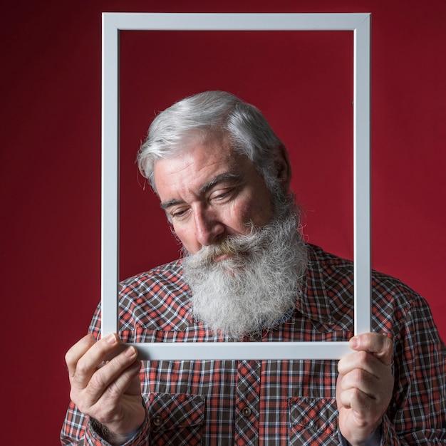 Senior homme déprimé tenant un cadre de bordure blanche devant son visage sur un fond coloré Photo gratuit