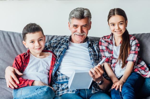 Senior homme avec deux jolis petits-enfants lisant un livre tout en s'installant sur le canapé. Photo Premium