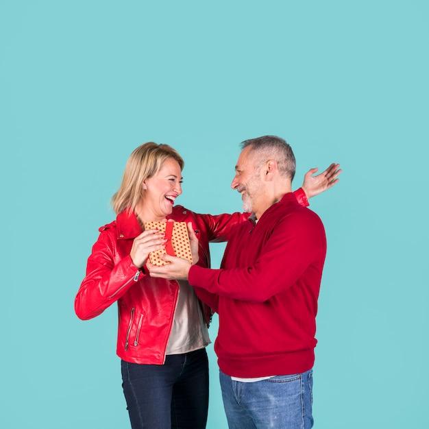 Senior homme donnant une boîte cadeau à sa femme blonde mature gaie Photo gratuit
