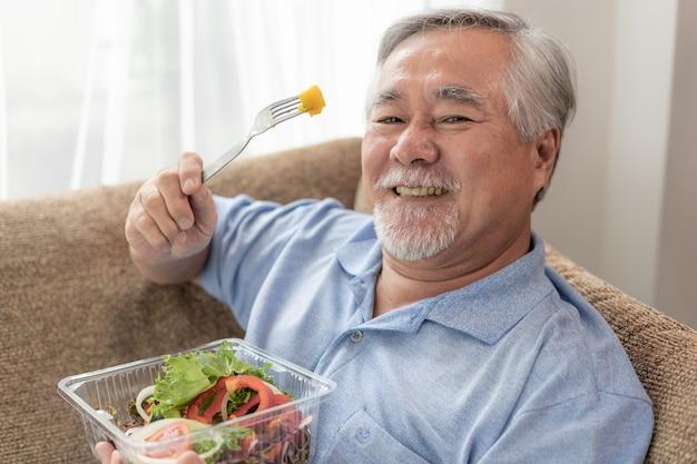 Senior homme lifestyle se sentir heureux profiter de manger des aliments diététiques salade fraîche sur le canapé Photo Premium