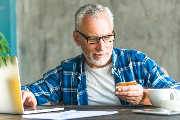 Senior homme lisant le numéro de carte de crédit tout en travaillant sur un ordinateur portable Photo gratuit