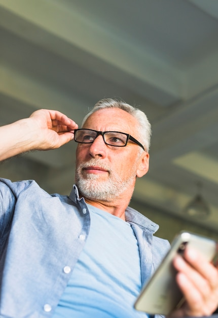 Senior homme avec la main sur les lunettes, tenant le téléphone portable Photo gratuit