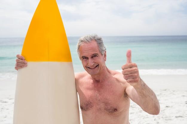 Senior homme avec planche de surf montrant les pouces vers le haut Photo Premium
