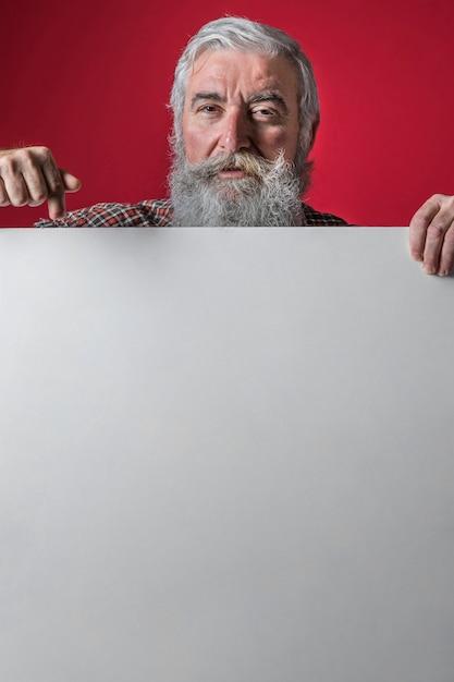 Senior homme pointant son doigt vers le bas sur une pancarte blanche vierge sur fond rouge Photo gratuit