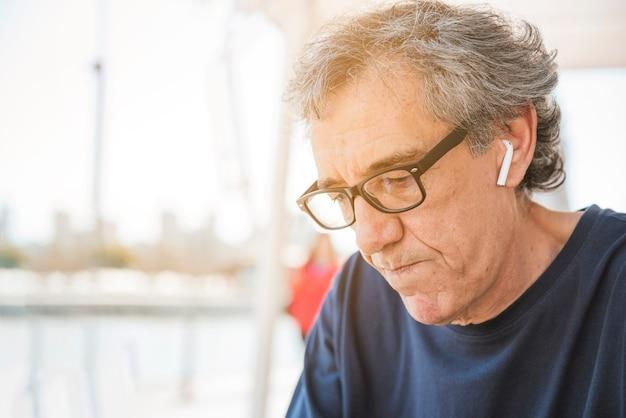 Senior homme portant des lunettes avec des écouteurs bluetooth blancs dans son oreille Photo gratuit