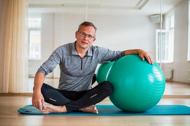 Senior homme prêt à utiliser le ballon d'exercice Photo gratuit