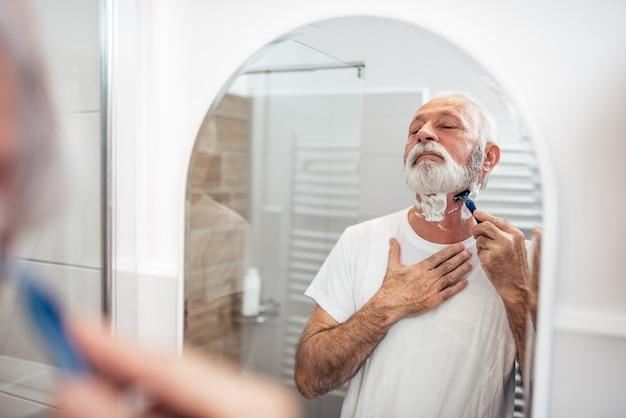 Senior Homme Rasage Dans La Salle De Bain, Reflet Dans L'image Miroir. Photo Premium