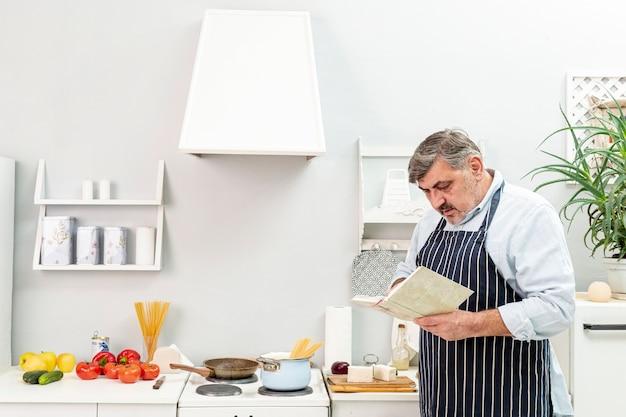 Senior Homme à La Recherche Dans Un Livre De Cuisine Photo gratuit