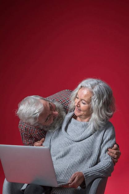 Senior homme regardant sa femme assise sur une chaise tenant un ordinateur portable ouvert sur fond rouge Photo gratuit