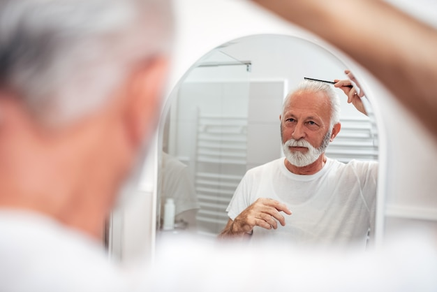Senior Homme Se Peigner Les Cheveux Dans La Salle De Bain. Photo Premium