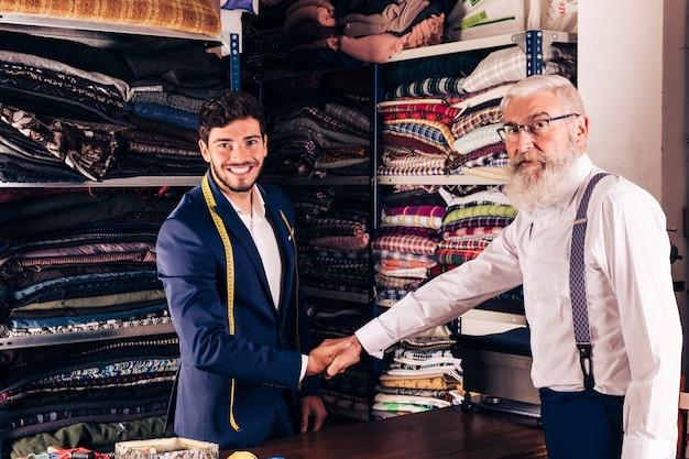 Senior homme serrant la main avec souriant jeune tailleur masculin dans son magasin Photo gratuit