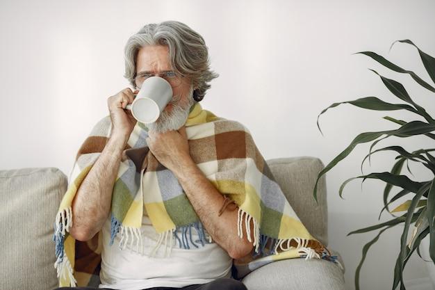 Senior Homme Seul Assis Sur Un Canapé. Homme Malade Recouvert De Plaid. Grangfather Avec Une Tasse De Thé. Photo gratuit